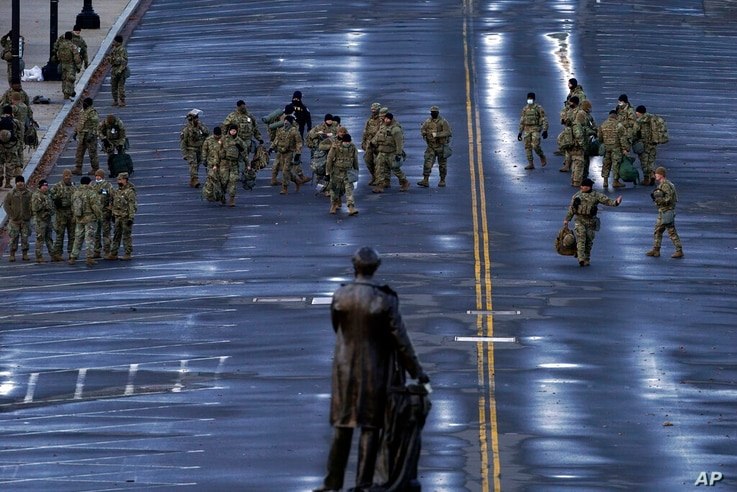 National Guard members walk in a security zone ahead of President-elect Joe Biden inauguration during the 59th Presidential…