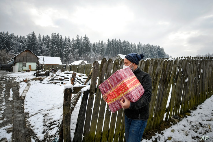 Valeriu Nicolae carries a box containing basic food, hygiene and medicinal products in Nucsoara, Romania, Jan. 9, 2021.