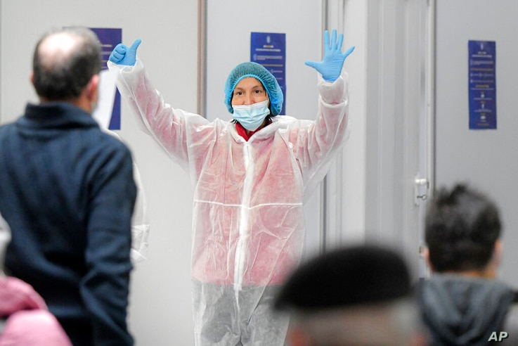 A member of the medical gestures to indicate the number of the vaccination booth, at a Pfizer-BioNTech COVID-19 vaccination…