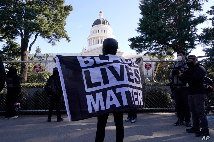 """A demonstrator holds a """"Black Lives Matter"""" flag during a protest at the state Capitol in Sacramento, Calif., Wednesday, Jan…"""