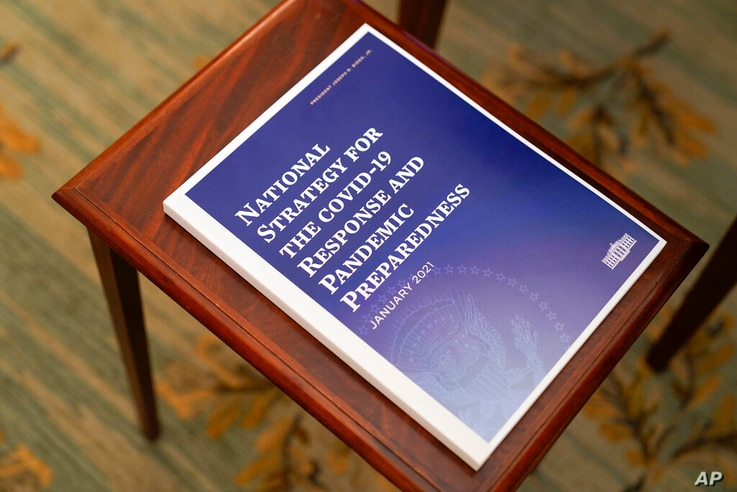A booklet titled 'National Strategy for the Covid-19 Response and Pandemic Preparedness' rests on a table before President Joe...