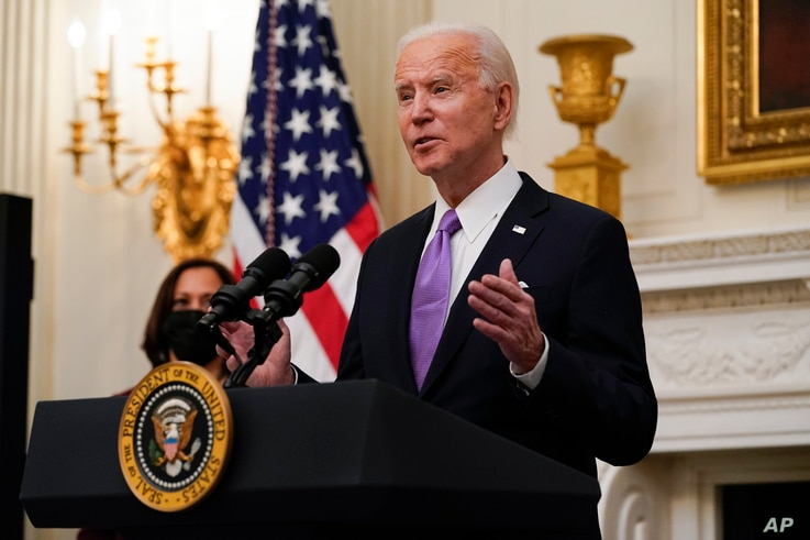 President Joe Biden speaks about the coronavirus, accompanied by Vice President Kamala Harris, in the State Dinning Room of the...