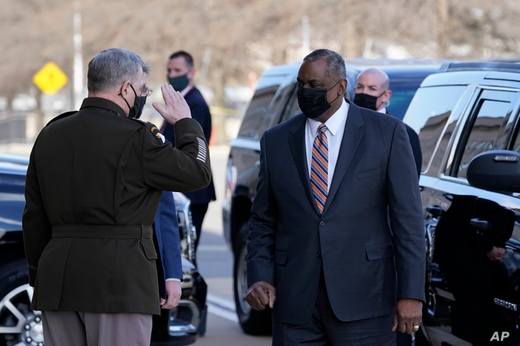 Defense Secretary Lloyd Austin, right, is saluted by Chairman of the Joint Chiefs of Staff Mark Milley as he arrives at the Pentagon, Jan. 22, 2021, in Washington.