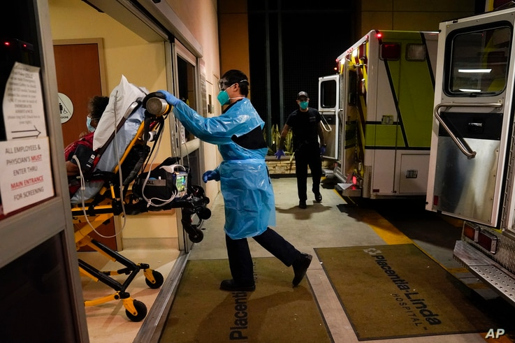 Emergency medical technician Thomas Hoang, 29, of Emergency Ambulance Service, pushes a gurney into an emergency room to drop…