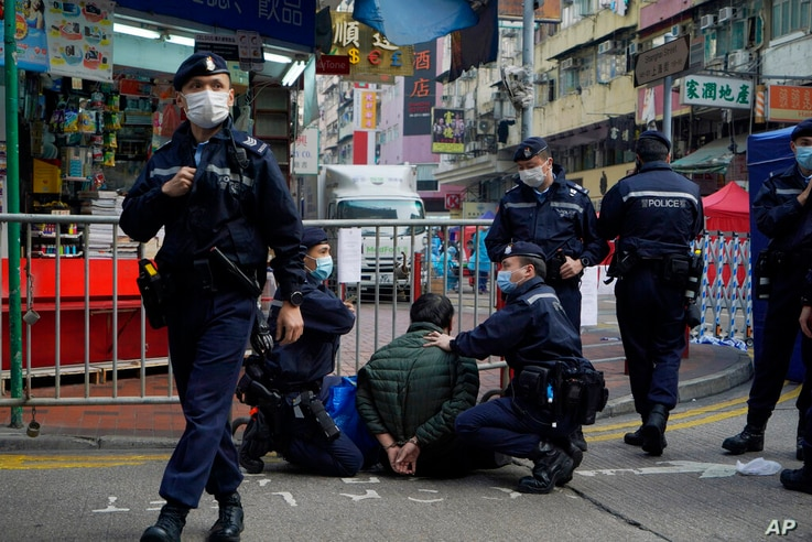 A man is detained after attacking a police officer as he wants to enter the closed area in Jordan area of Hong Kong, Saturday,...