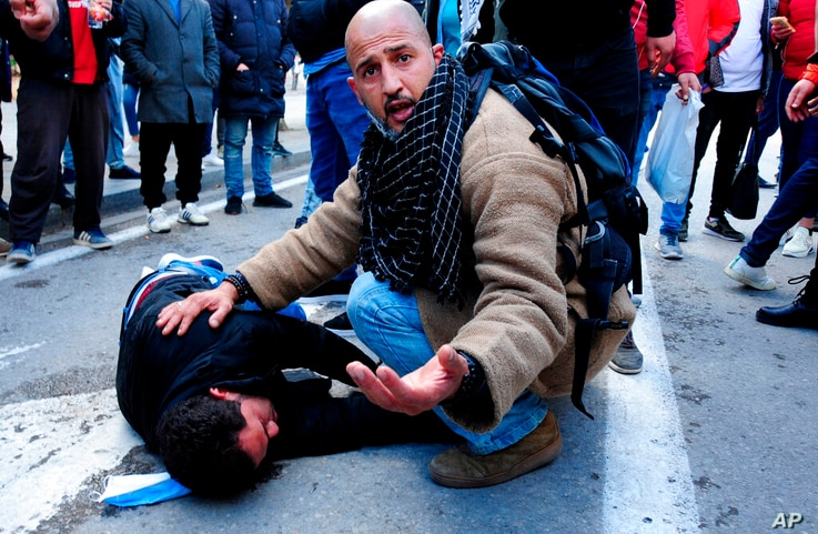 A demonstrator takes care of a man wounded by police forces during a demonstration in Tunis, Saturday, Jan.23, 2021. Tunisia is…