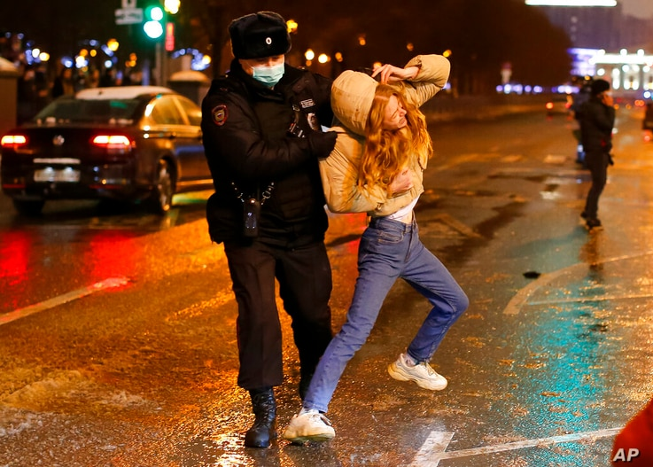 Riot police detain a young woman during a protest against the jailing of opposition leader Alexei Navalny in Pushkin square in…