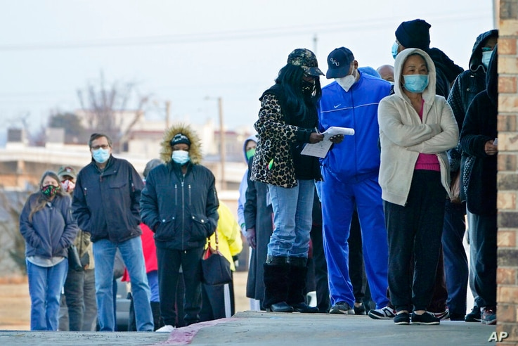 People wait in line to receive a COVID-19 vaccine at Ebenezer Baptist Church, Tuesday, Jan. 26, 2021, in Oklahoma City. Rev…