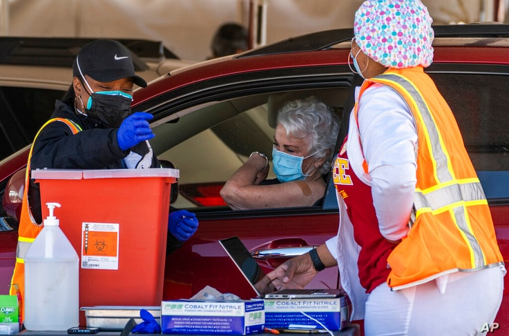 A woman is vaccinated inside her vehicle at a mass COVID-19 vaccination site outside The Forum in Inglewood, Calif., Tuesday,…