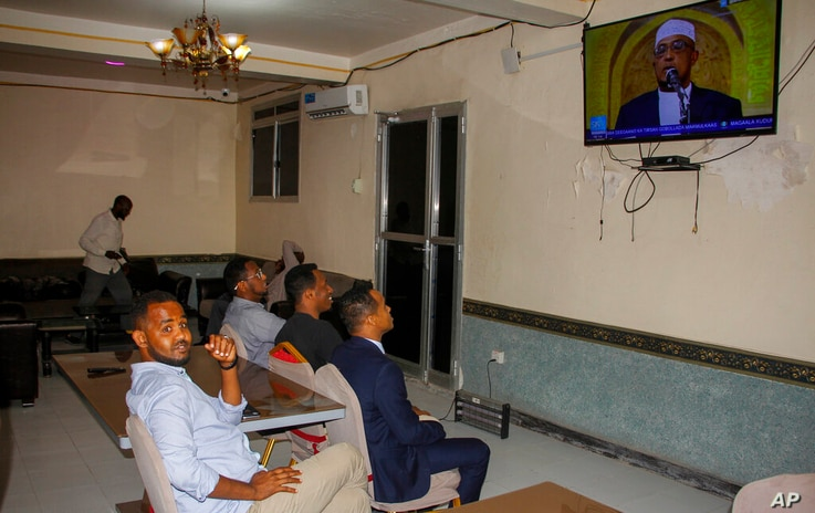 People watch news about the upcoming election on a television in Mogadishu, Somalia Thursday, Jan. 28, 2021. As Somalia marks…