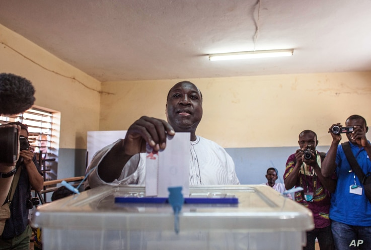 Burkina Faso presidential candidate from the UPC party Zephirin Diabre, center, casts his ballot during elections in…