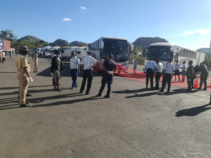 Immigration officers at Mwanza border wellcoming buses carrying Malawi returnees