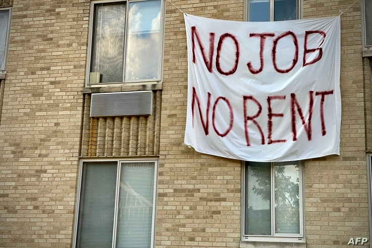 FILE - A banner against renters' evictions reading