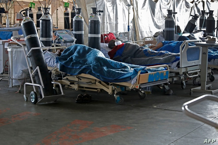 Patients are seen lying on hospital beds inside a temporary ward for possible COVID-19 coronavirus patients at Steve Biko Academic Hospital in Pretoria, South Africa.