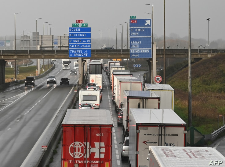 FILE - Trucks bound for Britain wait on the access ramp to the Channel Tunnel in Calais, northern France, before leaving for England, Dec. 17, 2020.