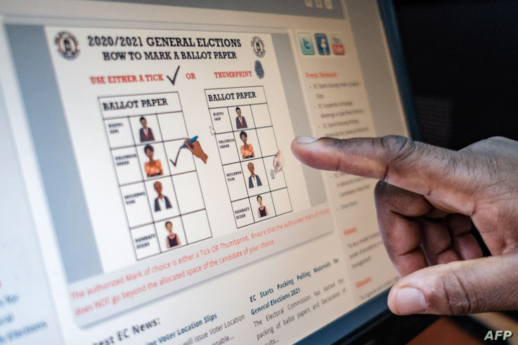 A staff member gestures towards a screen displaying how a ballot paper should be marked during the upcoming elections at the…
