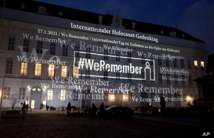 The words '#WeRemember' are displayed at the facade of the Austrian Parliament at the Hofburg palace in support of the campaign for the International Holocaust Remembrance Day in Vienna, Jan. 27, 2021.