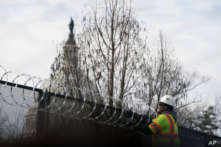 With the U.S. Capitol dome in the background, razor wire is installed to increase security ahead of the inauguration of President-elect Joe Biden and Vice President-elect Kamala Harris, in Washington, Jan. 17, 2021.