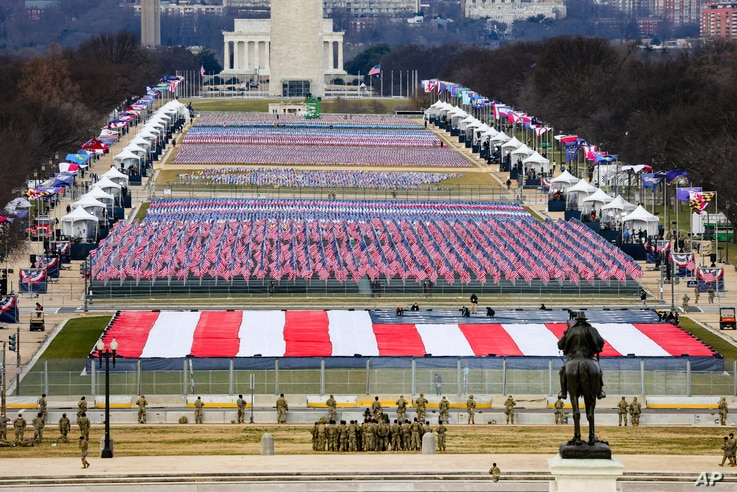 Members of the National Guard look on as American flags decorate the 'Field of Flags' at the National Mall ahead of President-elect Joe Biden's inauguration ceremony, Jan. 20, 2021, in Washington.
