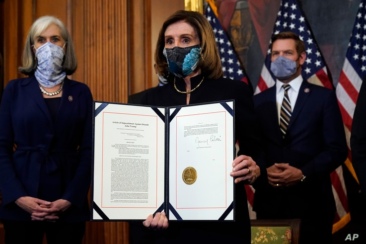 House Speaker Nancy Pelosi of Calif., displays the signed article of impeachment against President Donald Trump in an engrossment ceremony before transmission to the Senate for trial on Capitol Hill, in Washington, D.C., Jan. 13, 2021.