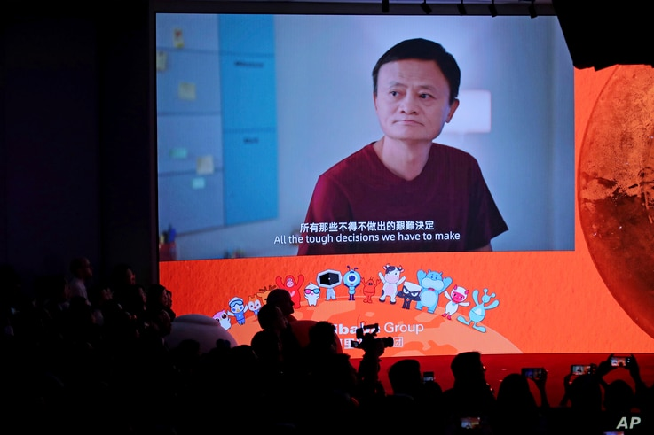FILE - A screen shows footage of Alibaba Group co-founder Jack Ma during the Alibaba Group's listing ceremony at the Hong Kong Stock Exchange (HKEX) in Hong Kong, Nov. 26, 2019.