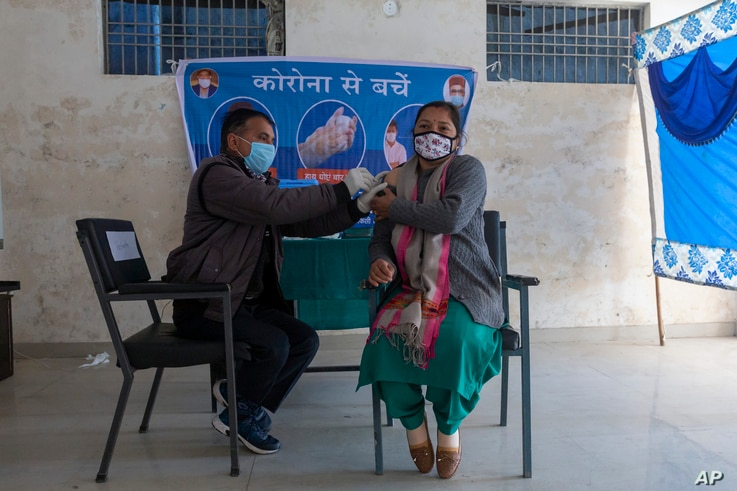 A health worker pretends to administer a shot of a COVID-19 vaccine to a volunteer during a mock vaccination drill at a school in Dharmsala, India, Jan. 11, 2021.