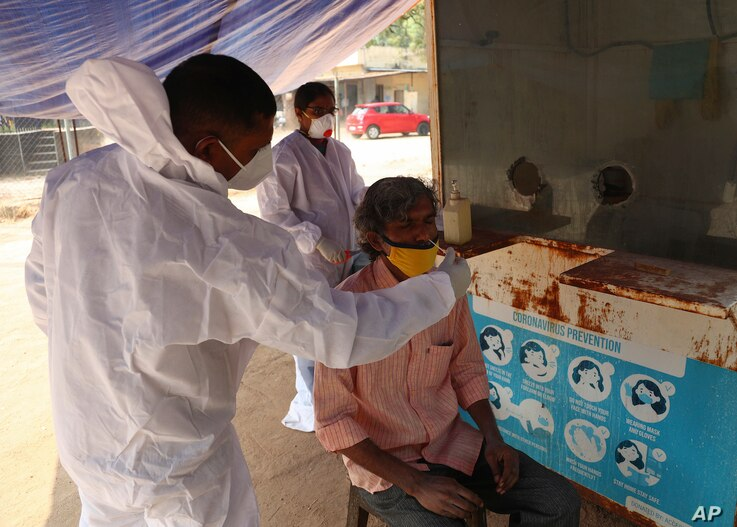 A health worker takes a nasal swab sample of a man at a COVID-19 testing center in Hyderabad, India, Jan. 2, 2021.
