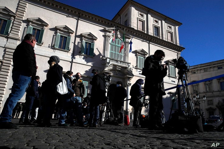 Reporters stand at the entrance of Rome's Quirinale Presidential Palace, Jan. 26, 2021, ahead of Prime Minister Giuseppe Conte offering his resignation.