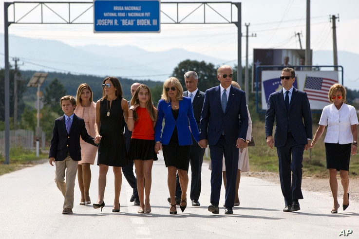 FILE - Then U.S. Vice President Joe Biden joined by his family members walk along the national road named after his late son Joseph R. 'Beau' Biden III, in the village of Sojevo, Kosovo, Aug. 17, 2016.