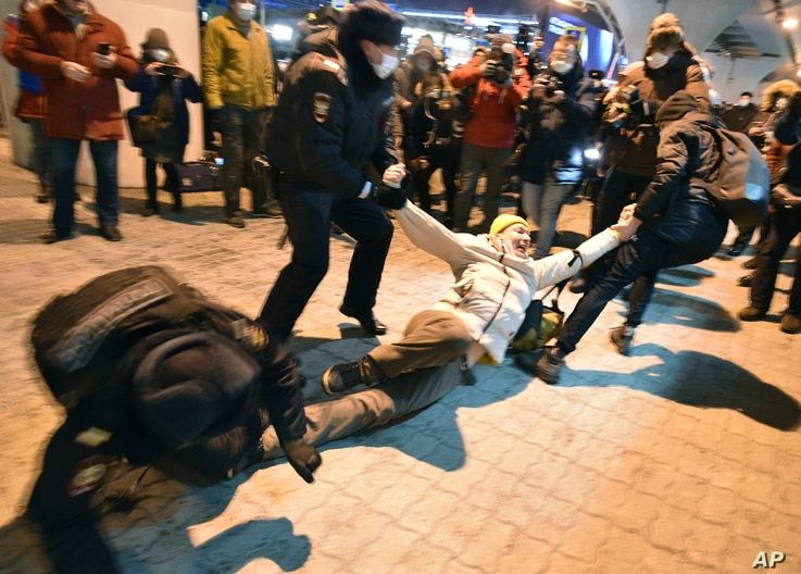 Police officers detain a man at Moscow's Vnukovo airport where Russian opposition leader Alexei Navalny is expected to arrive, outside Moscow, Russia, Jan. 17, 2021.