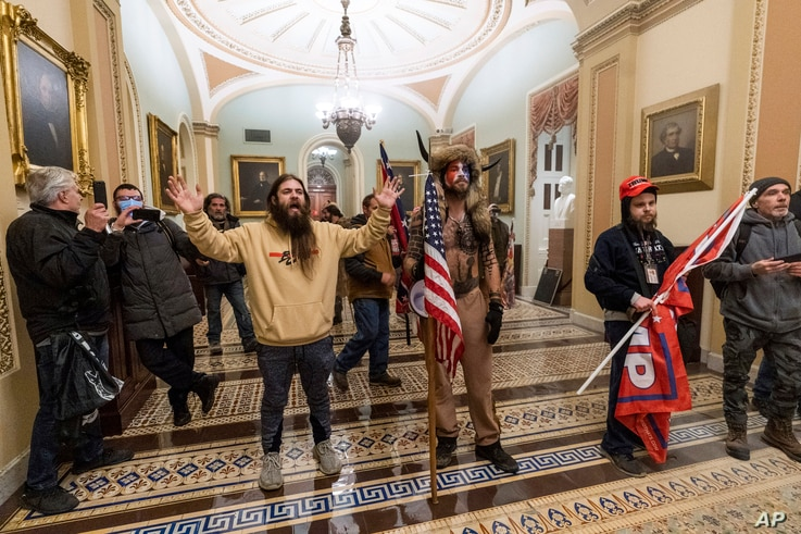 FILE - Supporters of President Donald Trump are confronted by U.S. Capitol Police officers outside the Senate Chamber inside the Capitol in Washington, Jan. 6, 2021.
