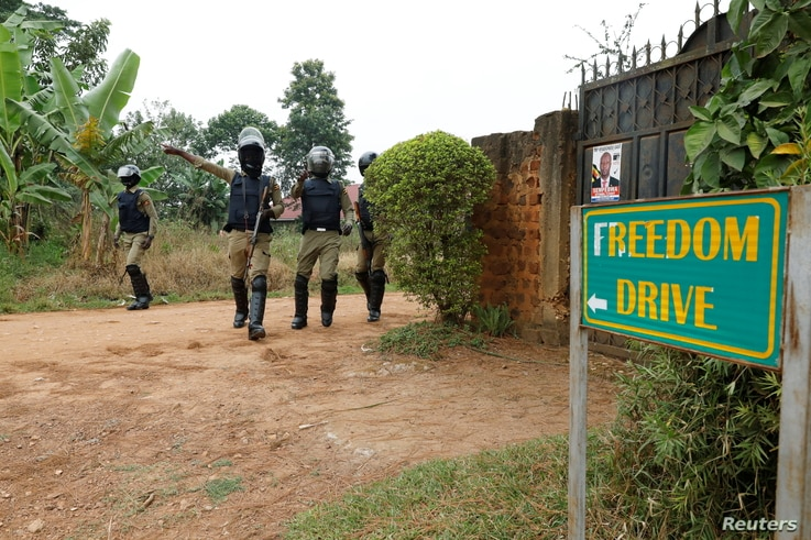 FILE - Ugandan police officers order journalists to leave a road leading to the home of Ugandan opposition presidential candidate Robert Kyagulanyi, also known as Bobi Wine, in Kampala, Uganda, Jan. 16, 2021.