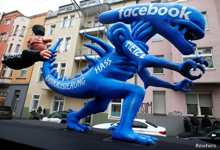 FILE - A figure representing hate speech on Facebook is seen featured during a carnival parade in Duesseldorf, Germany, Feb. 24, 2020.