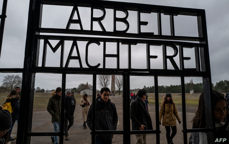 "Visitors walk past the gate, inscribed with the words: ""Arbeit Macht Frei"" (Work makes you free) of the former Sachsenhausen…"