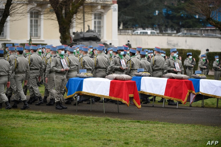 Servicemen of the '1er Regiment de Chasseurs' (1st Hunter Regiment) stand by the coffins of the three French soldiers who were…