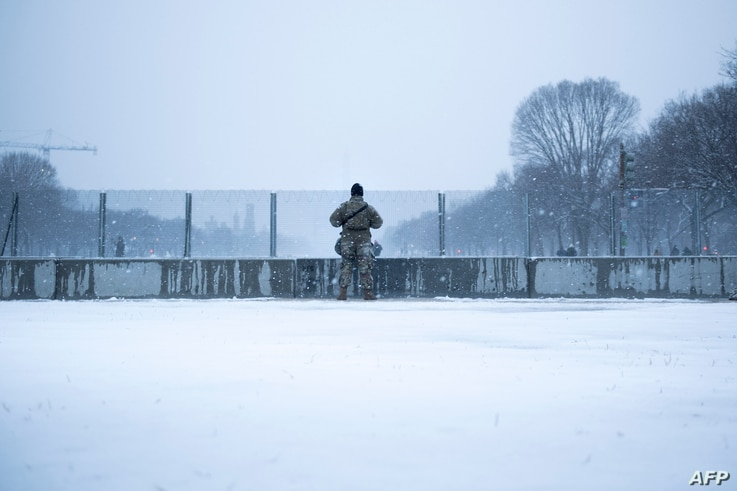 A member of the National Guard watches over the National Mall after increased security measures put in place after the January…