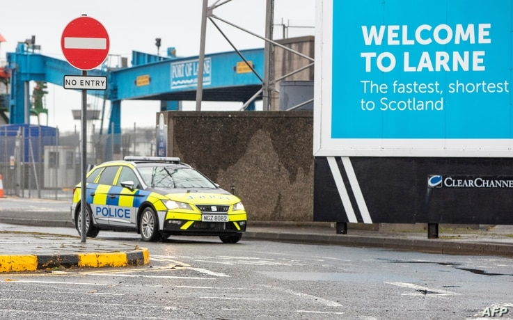 A police vehicle patrols at the Port of Larne in County Antrim, Northern Ireland on February 2, 2021 after threats were made to…