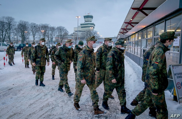 Soldiers of the German armed forces Bundeswehr wear face masks as they enter the new vaccination center on the day of its…