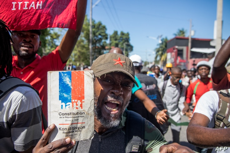 Demonstrators march in Port-au-Prince on February 10, 2021, to protest against the government of President Jovenel Moise. -…