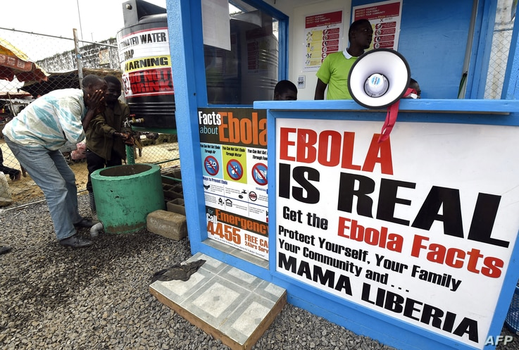 (FILES) In this file photograph taken on September 30, 2014, Liberians wash their hands next to an Ebola information and…