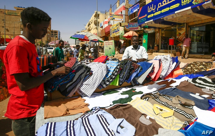 A street vendor displays shirts at a market in the Sudanese capital Khartoum on February 21, 2021. - Sudan said today it was...