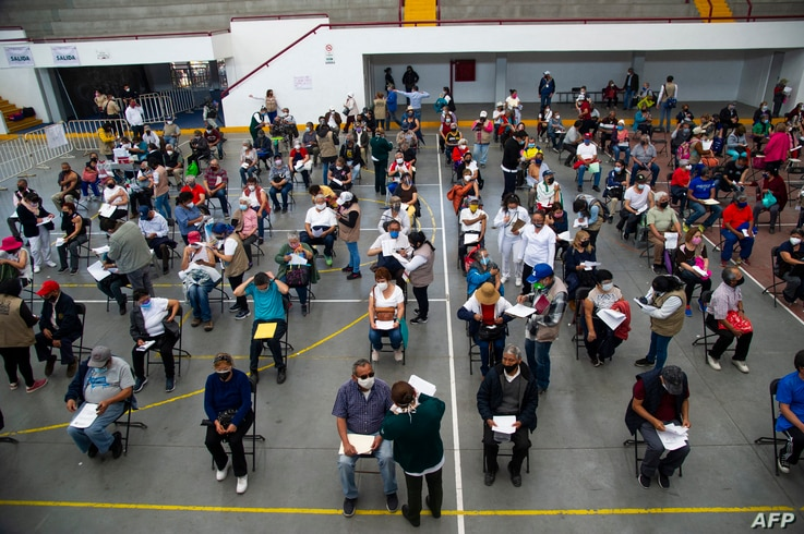 People wait to receive the first dose of China's Sinovac Biotech CoronaVac vaccine against COVID-19, in Ecatepec, Mexico state,…