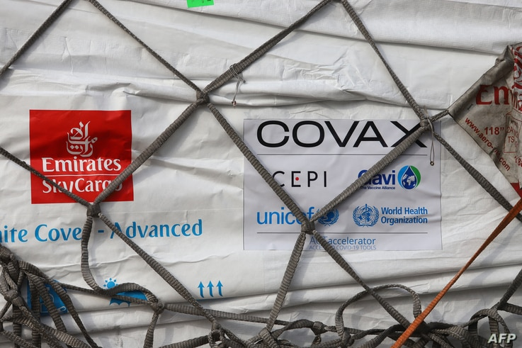 This photograph taken on February 24, 2021 shows an Emirates Airlines logo next to a Covax tag on a shipment of Covid-19…