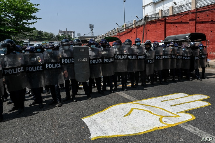 Riot police stand guard on a road, behind a street mural of the protesters' three finger salute, after a clash between pro…