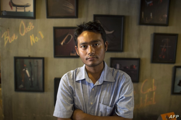 This picture taken on March 28, 2017 shows poet Maung Saungkha posing in Yangon. - One year after Aung San Suu Kyi's National…