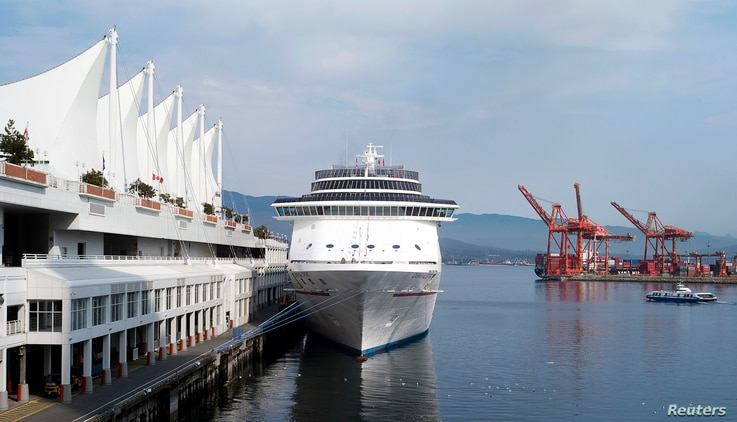 The Carnival Spirit cruise ship sits docked at Canada Place as a seabus (R) commuter boat makes its way across the inner…