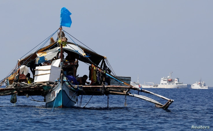 A Philippine fishing boat is seen anchored near China Coast Guard vessels patrolling at the disputed Scarborough Shoal April 5,…