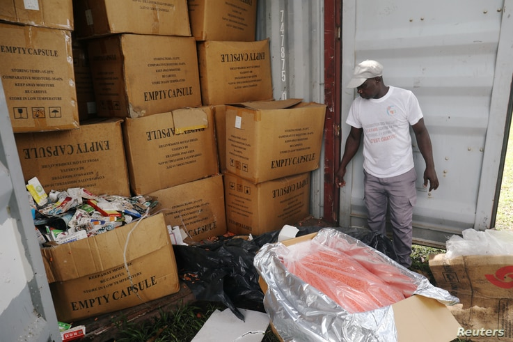 An agent stands next to a container full of illegal and false drugs seized by Ivorian authorities in Abidjan, Ivory Coast…