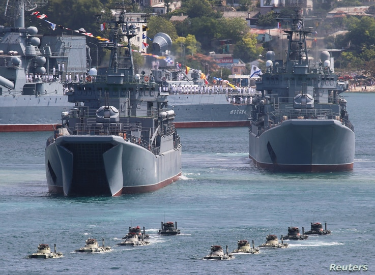 Russian armoured personnel carriers submerge from amphibious assault ships during the Navy Day parade in the Black Sea port of…