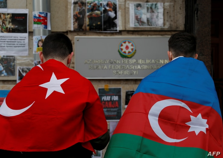 Men holding national flags of Azerbaijan and Turkey stand next to a makeshift memorial for people killed in Azerbaijan during…